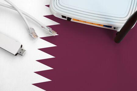 Katar-Flagge auf dem Tisch mit Internet-Rj45-Kabel, drahtlosem USB-WLAN-Adapter und Router dargestellt. Internetverbindungskonzept