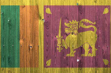 Flaga Sri Lanki przedstawiona w jasnych kolorach farby na starej drewnianej ścianie z bliska. Teksturowany baner na szorstkim tle Zdjęcie Seryjne