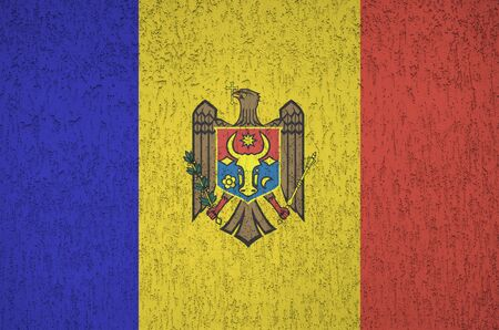 Moldova flag depicted in bright paint colors on old relief plastering wall close up. Textured banner on rough background
