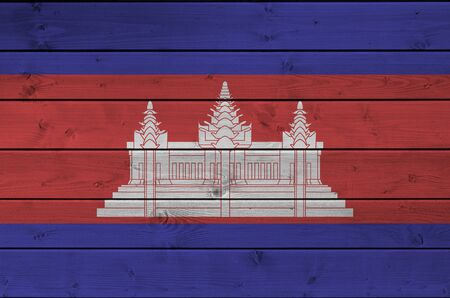 Cambodia flag depicted in bright paint colors on old wooden wall close up. Textured banner on rough background