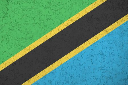 Tanzania flag depicted in bright paint colors on old relief plastering wall close up. Textured banner on rough background