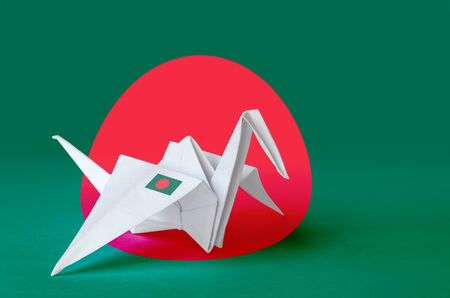 Bangladesh flag depicted on paper origami crane wing. Oriental handmade arts concept Stock Photo