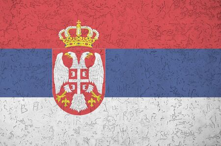 Serbia flag depicted in bright paint colors on old relief plastering wall close up. Textured banner on rough background