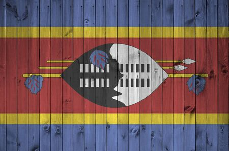 Swaziland flag depicted in bright paint colors on old wooden wall close up. Textured banner on rough background Stock fotó
