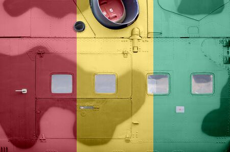 Guinea flag depicted on side part of military armored helicopter close up. Army forces aircraft conceptual background
