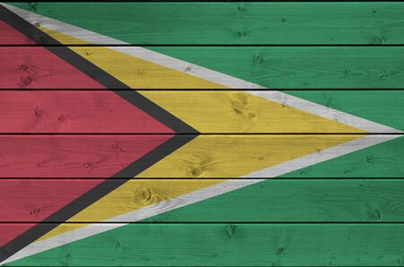 Guyana flag depicted in bright paint colors on old wooden wall close up. Textured banner on rough background