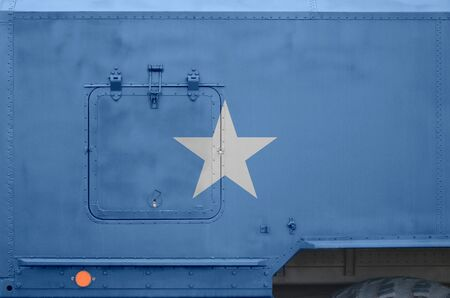 Somalia flag depicted on side part of military armored truck close up. Army forces vehicle conceptual background