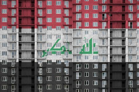 Iraq flag depicted in paint colors on multi-storey residental building under construction. Textured banner on big brick wall background Archivio Fotografico