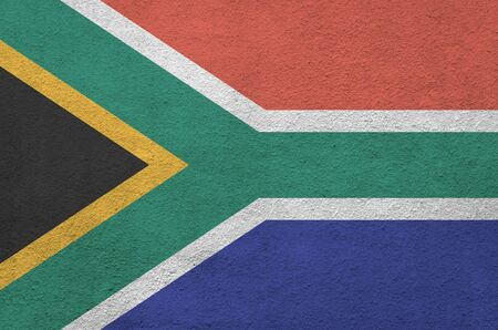 South Africa flag depicted in bright paint colors on old relief plastering wall close up. Textured banner on rough background