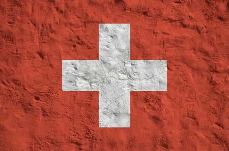 Switzerland flag depicted in bright paint colors on old relief plastering wall close up. Textured banner on rough background