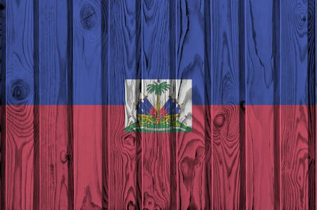 Haiti flag depicted in bright paint colors on old wooden wall close up. Textured banner on rough background