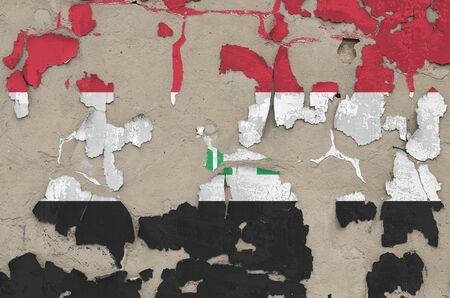 Iraq flag depicted in paint colors on old obsolete messy concrete wall close up. Textured banner on rough background