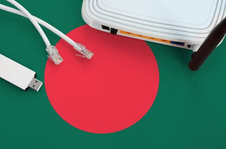 Bangladesh flag depicted on table with internet rj45 cable, wireless usb wifi adapter and router. Internet connection concept