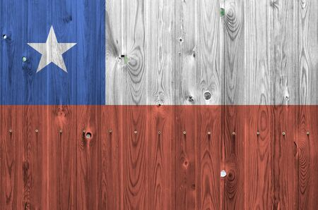 Chile flag depicted in bright paint colors on old wooden wall close up. Textured banner on rough background