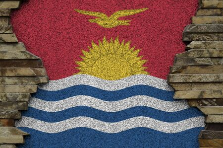 Kiribati flag depicted in paint colors on old stone wall close up. Textured banner on rock wall background