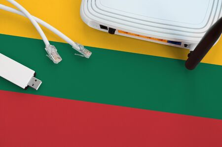 Lithuania flag depicted on table with internet rj45 cable, wireless usb wifi adapter and router. Internet connection concept