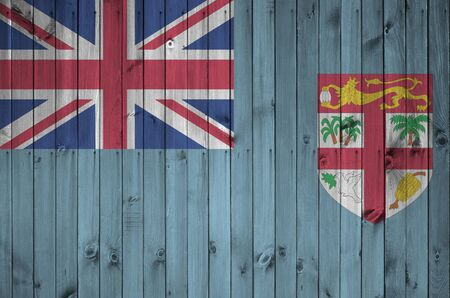 Fiji flag depicted in bright paint colors on old wooden wall close up. Textured banner on rough background