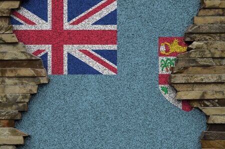 Fiji flag depicted in paint colors on old stone wall close up. Textured banner on rock wall background