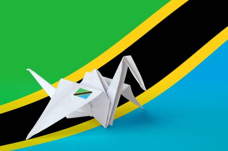 Tanzania flag depicted on paper origami crane wing. Oriental handmade arts concept