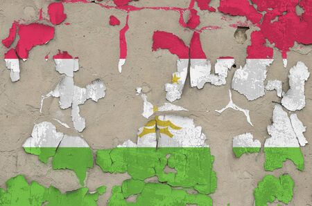 Tajikistan flag depicted in paint colors on old obsolete messy concrete wall close up. Textured banner on rough background