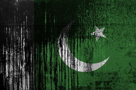 Pakistan flag depicted in paint colors on old and dirty oil barrel wall close up. Textured banner on rough background Stock Photo