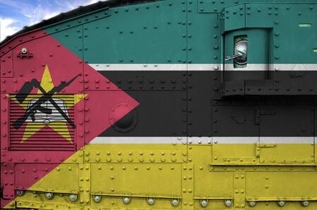 Mozambique flag depicted on side part of military armored tank close up. Army forces conceptual background