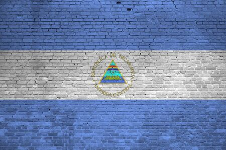 Nicaragua flag depicted in paint colors on old brick wall close up. Textured banner on big brick wall masonry background