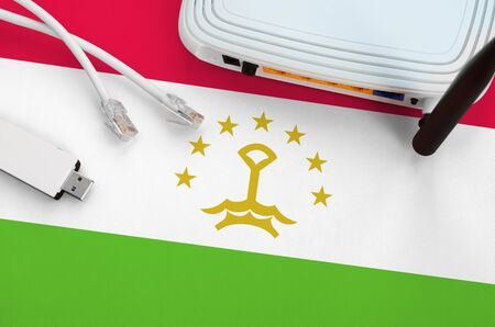 Tajikistan flag depicted on table with internet rj45 cable, wireless usb wifi adapter and router. Internet connection concept