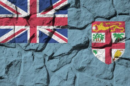 Fiji flag depicted in paint colors on old stone wall close up. Textured banner on rock wall background Stock fotó