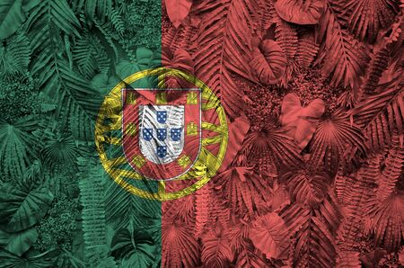 Portugal flag depicted on many leafs of monstera palm trees. Trendy fashionable background