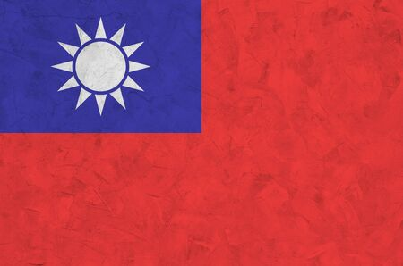 Taiwan flag depicted in bright paint colors on old relief plastering wall close up. Textured banner on rough background