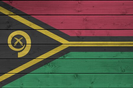 Vanuatu flag depicted in bright paint colors on old wooden wall close up. Textured banner on rough background