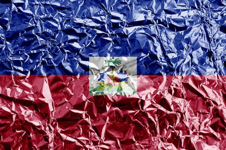 Haiti flag depicted in paint colors on shiny crumpled aluminium foil close up. Textured banner on rough background Stock fotó