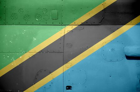 Tanzania flag depicted on side part of military armored helicopter close up. Army forces aircraft conceptual background Stock fotó