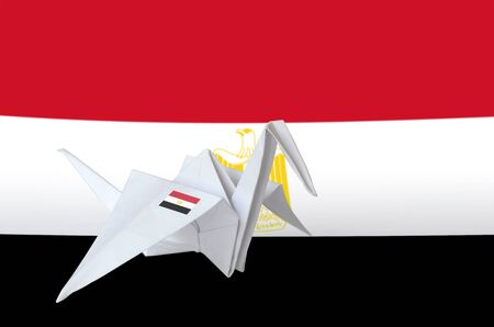 Egypt flag depicted on paper origami crane wing. Oriental handmade arts concept