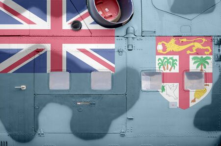 Fiji flag depicted on side part of military armored helicopter close up. Army forces aircraft conceptual background Stock fotó