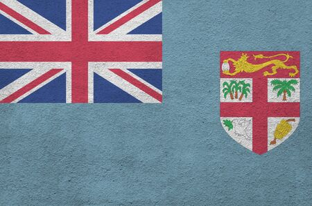 Fiji flag depicted in bright paint colors on old relief plastering wall close up. Textured banner on rough background