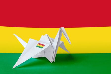 Bolivia flag depicted on paper origami crane wing. Oriental handmade arts concept