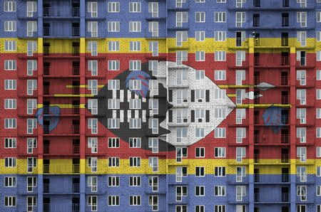 Swaziland flag depicted in paint colors on multi-storey residental building under construction. Textured banner on big brick wall background