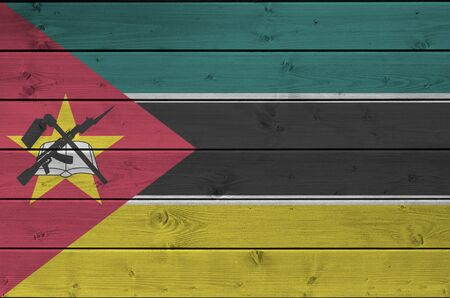 Mozambique flag depicted in bright paint colors on old wooden wall close up. Textured banner on rough background Stock fotó