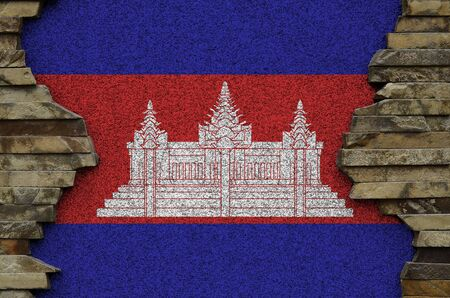 Cambodia flag depicted in paint colors on old stone wall close up. Textured banner on rock wall background