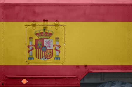 Spain flag depicted on side part of military armored truck close up. Army forces vehicle conceptual background Banco de Imagens