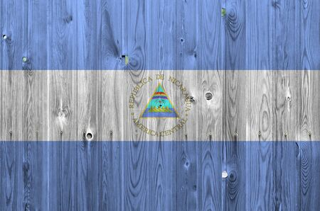 Nicaragua flag depicted in bright paint colors on old wooden wall close up. Textured banner on rough background Stock fotó