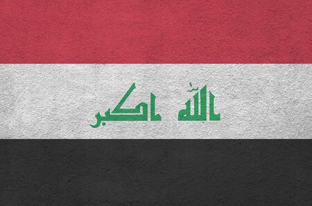 Iraq flag depicted in bright paint colors on old relief plastering wall close up. Textured banner on rough background Imagens