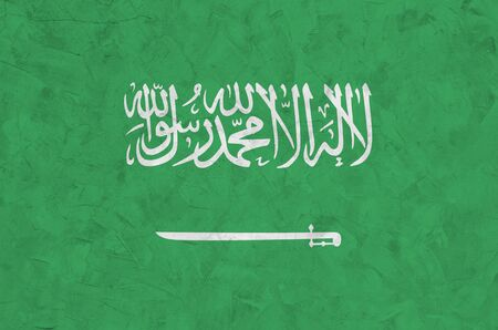 Saudi Arabia flag depicted in bright paint colors on old relief plastering wall close up. Textured banner on rough background