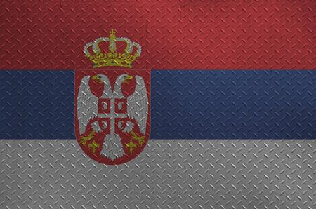 Serbia flag depicted in paint colors on old brushed metal plate or wall close up. Textured banner on rough background