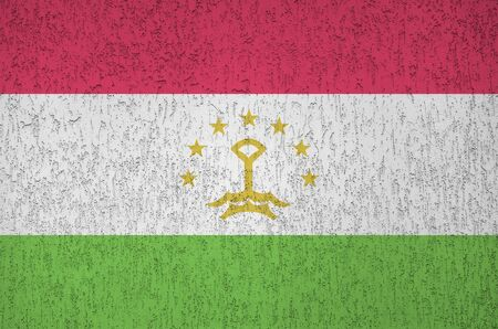 Tajikistan flag depicted in bright paint colors on old relief plastering wall close up. Textured banner on rough background Stock fotó