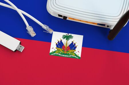 Haiti flag depicted on table with internet rj45 cable, wireless usb wifi adapter and router. Internet connection concept