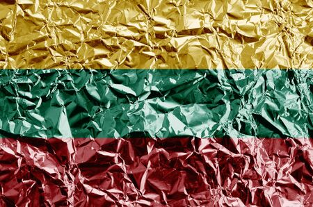Lithuania flag depicted in paint colors on shiny crumpled aluminium foil close up. Textured banner on rough background