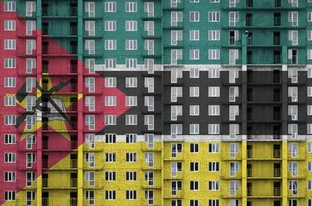 Mozambique flag depicted in paint colors on multi-storey residental building under construction. Textured banner on big brick wall background